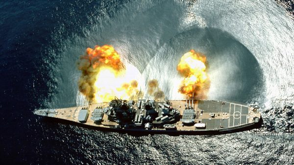 An overhead view of the battleship USS IOWA (BB-61) firing all 15 of its guns (nine 16-inch and six 5-inch) during a target exercise near Vieques Island.  Careful observation of the three main turrets shows the barrels in various states of recoil.