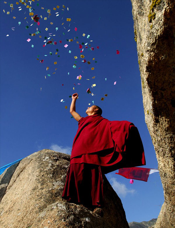 A-monk-in-crimson-robe-scatters-the-colorful-sutra-streamers-which-symbol-auspiciousness-into-the-wallpaper-wp3002902