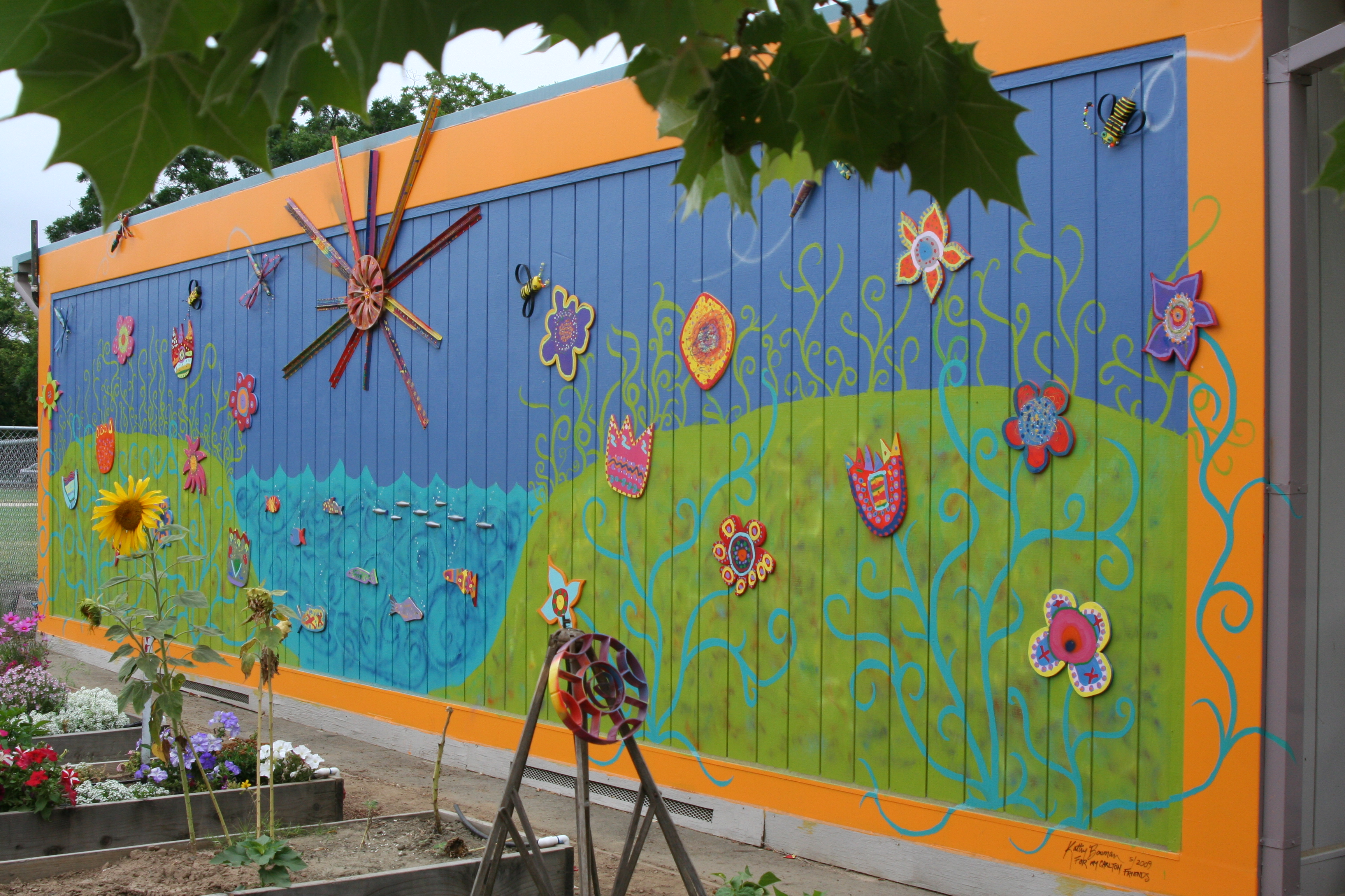 A-mural-painted-at-a-school-The-sun-dragonflies-bees-and-fish-were-all-made-from-materials-found-wallpaper-wp3002904