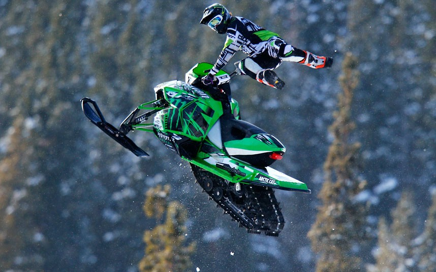 A-snowmobile-flies-through-the-air-as-part-of-the-entertainment-during-the-Monster-Energy-Snowmobil-wallpaper-wp4404037