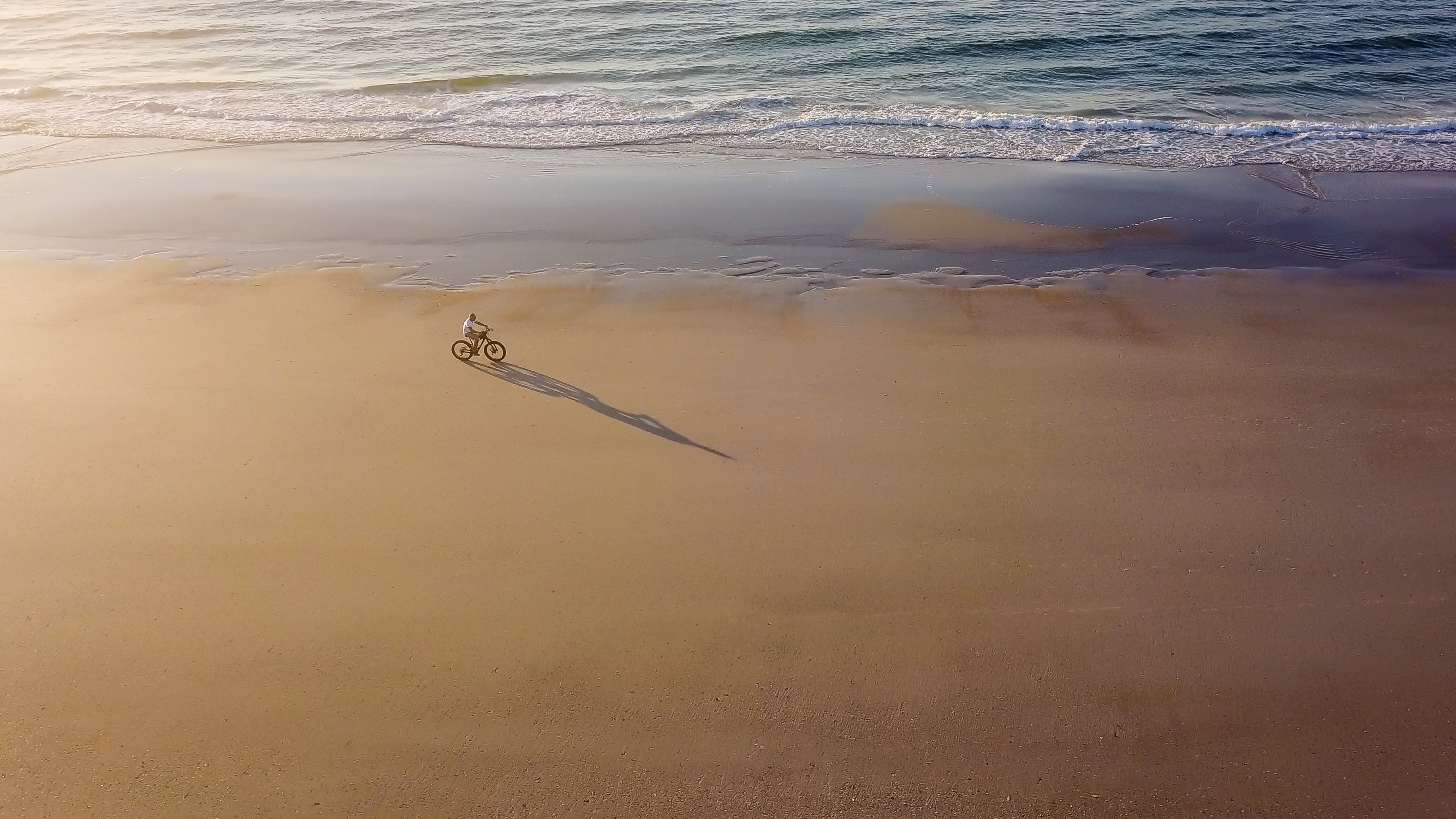 A-Man-Riding-His-Bike-on-the-Beach-x-OC-wallpaper-wp5203673