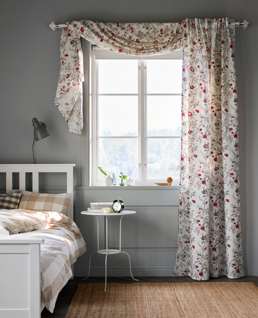 A-floral-printed-curtain-hangs-in-a-window-in-a-bedroom-wallpaper-wp5803198