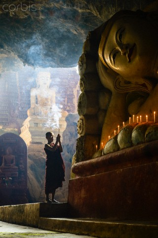 Asian-monk-lighting-incense-in-temple-wallpaper-wp3003346