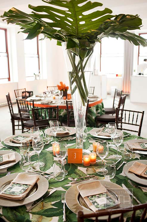 Clusters-of-orange-votive-candles-surround-a-tall-vase-overflowing-with-bright-banana-leaves-wallpaper-wp4805374