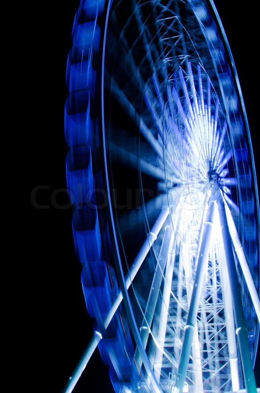 Ferris-wheel-in-motion-in-a-night-time-background-Stock-Photo-wallpaper-wpc9004911
